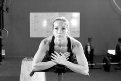 Mujer joven en la máquina abdominal del crujido - entrenamiento del crossfit Foto de archivo