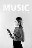 Mujer joven en la música que escucha de los auriculares que se relaja en casa Fotografía de archivo libre de regalías
