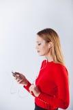 Mujer joven en la música que escucha de los auriculares que se relaja en casa Foto de archivo