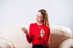 Mujer joven en la música que escucha de los auriculares que se relaja en casa encendido tan Imagen de archivo libre de regalías