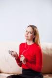 Mujer joven en la música que escucha de los auriculares que se relaja en casa encendido tan Imágenes de archivo libres de regalías