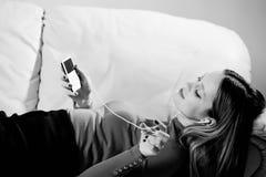 Mujer joven en la música que escucha de los auriculares que se relaja en casa encendido tan Fotografía de archivo