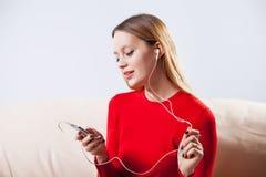 Mujer joven en la música que escucha de los auriculares que se relaja en casa encendido tan Imagenes de archivo