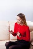 Mujer joven en la música que escucha de los auriculares que se relaja en casa encendido tan Fotos de archivo
