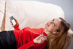 Mujer joven en la música que escucha de los auriculares que se relaja en casa encendido tan Imagen de archivo