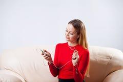 Mujer joven en la música que escucha de los auriculares que se relaja en casa encendido tan Foto de archivo