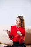 Mujer joven en la música que escucha de los auriculares que se relaja en casa encendido tan Foto de archivo libre de regalías
