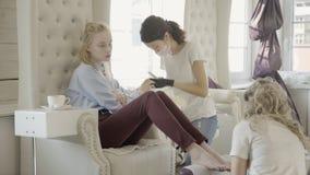 Mujer joven en la manicura y la sesión de la pedicura en salón de belleza almacen de metraje de vídeo