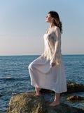 Mujer joven en la mirada de piedra del mar derecho Imagen de archivo libre de regalías