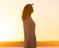 Mujer joven en la mirada ligera de la puesta del sol lejos Imágenes de archivo libres de regalías