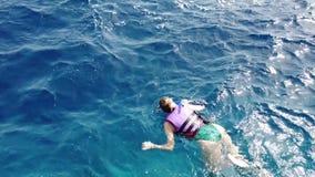 Mujer joven en la natación del traje de baño en máscara y tubo que bucean Arrecife de coral que bucea y de observación de la much metrajes