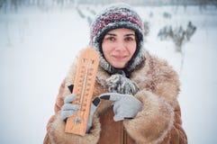 Mujer joven en la nieve con un termómetro Imagen de archivo libre de regalías