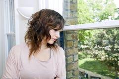 Mujer joven en la oficina de moda que mira hacia fuera la ventana Fotografía de archivo libre de regalías