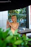 Mujer joven en la opinión urbana de fotografía del vestido con el teléfono móvil Imagenes de archivo