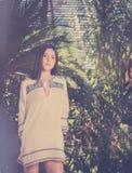 Mujer joven en la palmera tropical del clima que la rodea Foto de archivo