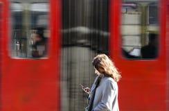 Mujer joven en la parada de autobús que mira el teléfono móvil Fotos de archivo libres de regalías