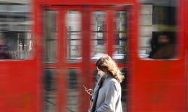 Mujer joven en la parada de autobús que mira el teléfono móvil Foto de archivo libre de regalías