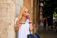 Mujer joven en la pared en la calle con café Imágenes de archivo libres de regalías