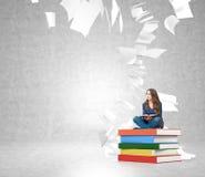 Mujer joven en la pila de libros con el vuelo de papel alrededor Imagenes de archivo