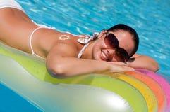 Mujer joven en la piscina Fotos de archivo