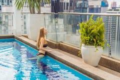 Mujer joven en la piscina entre los rascacielos y la ciudad grande Relájese en la ciudad grande Resto de la tensión imágenes de archivo libres de regalías