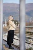 Mujer joven en la plataforma del ferrocarril del borde Imagen de archivo libre de regalías