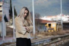 Mujer joven en la plataforma del ferrocarril del borde Foto de archivo
