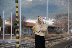 Mujer joven en la plataforma del ferrocarril del borde Imagenes de archivo