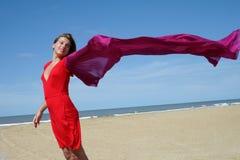 Mujer joven en la playa con la bufanda que agita roja Fotos de archivo libres de regalías