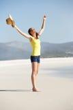 Mujer joven en la playa con las manos abiertas de par en par Foto de archivo