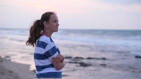 Mujer joven en la playa del mar que mira puesta del sol y ondas almacen de video