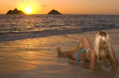 Mujer joven en la playa en la salida del sol foto de archivo