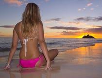Mujer joven en la playa en la salida del sol Foto de archivo libre de regalías