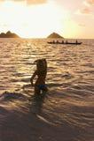 Mujer joven en la playa en la salida del sol fotos de archivo libres de regalías