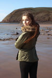 Mujer joven en la playa envuelta todo para arriba contra el viento Imagen de archivo libre de regalías