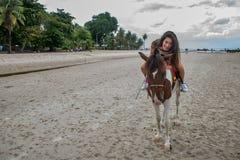 Mujer joven en la playa que abraza el caballo foto de archivo libre de regalías