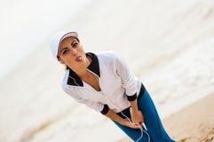 Mujer joven en la playa que escucha la música imagenes de archivo
