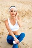 Mujer joven en la playa que escucha la música imágenes de archivo libres de regalías