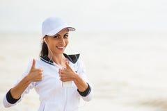 Mujer joven en la playa que escucha la música foto de archivo