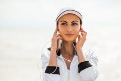 Mujer joven en la playa que escucha la música fotografía de archivo