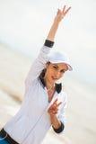 Mujer joven en la playa que escucha la música imagen de archivo