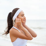 Mujer joven en la playa que escucha la música fotos de archivo