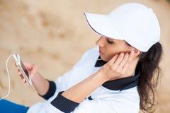 Mujer joven en la playa que escucha la música foto de archivo libre de regalías