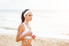 Mujer joven en la playa que escucha la música fotografía de archivo libre de regalías