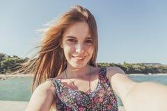 Mujer joven en la playa que mira la cámara Imagen de archivo
