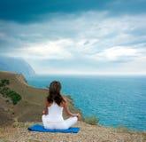 Mujer que hace yoga en el mar y las montañas imagenes de archivo