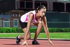 Mujer joven en la posición sprinting fotografía de archivo