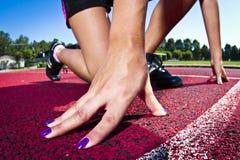 Mujer joven en la posición sprinting Fotografía de archivo libre de regalías