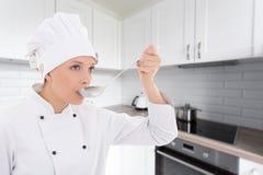 Mujer joven en la prueba del uniforme del cocinero algo en cocina Imagen de archivo