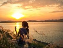 Mujer joven en la puesta del sol fotos de archivo